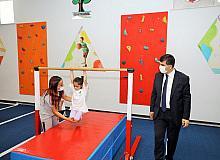 Anne ve babalar çocuklarıyla birlikte spor yapıyor